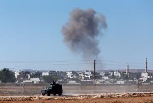 A Turkish forces armoured vehicle patrols the border road at the Turkey-Syria border, as background smoke rises after an airstrike in Kobani, Syria on Tuesday, Oct. 7, 2014. (AP / Lefteris Pitarakis)