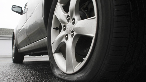 A car with a flat tire stands in an apartment complex's parking lot. (CP Images)