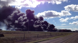 Black smoke billows from the scene of a train derailment near Clair, Sask. on Tuesday. (Wadena News/Twitter)
