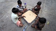 Impoverished children play a board game on a street in Kolkata, India, Saturday, June 4, 2011. (AP / Bikas Das)