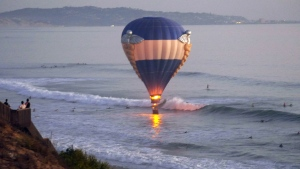In this Sunday, Oct. 5, 2014 photo provided by Jenny Parsons, a hot air balloon dips close to the ocean in Cardiff-by-the-Sea, a beach community in Encinitas, Calif. A man was proposing to his girlfriend during their sunset ride Sunday when the balloon drifted off course and hovered over the water, prompting a rescue by lifeguards and surfers. (AP / Jenny Parsons)
