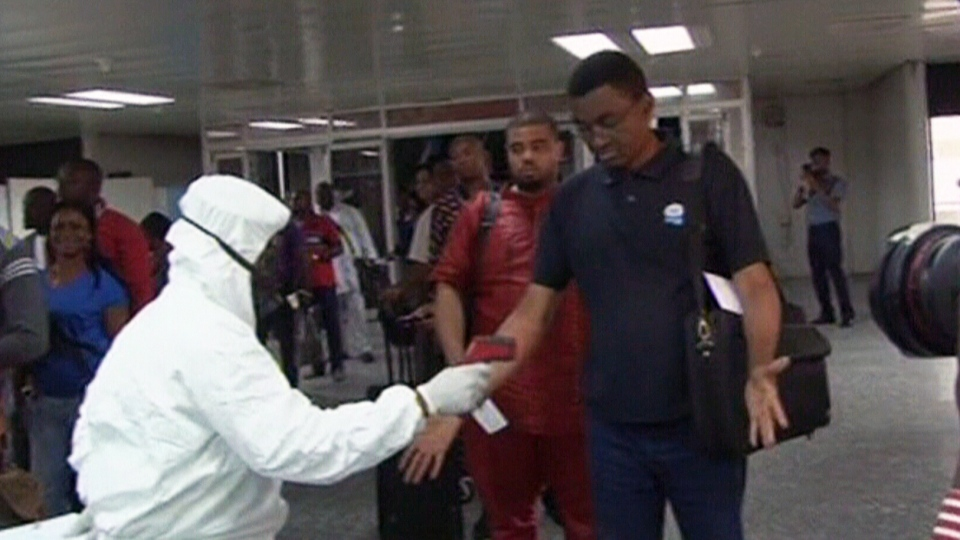 A Nigerian quarantine officer, left, checks the body temperature of a passenger against the possible infection of Ebola virus at an airport in Nigeria.