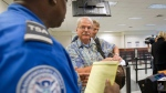 In this Oct. 4, 2011 file photo, passenger Don Heim, right, of Alpharetta, Ga., is briefed by Transportation Security Administration trainer Byron Gibson before going through a new expedited security line at Hartsfield-Jackson International Airport in Atlanta. (AP Photo/David Goldman)