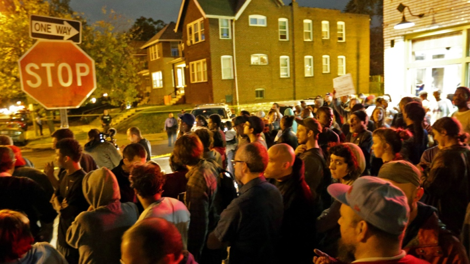 A crowd gathers near the scene in the 4100 block of Shaw Boulevard where a man was fatally shot by an off-duty St. Louis police officer on Wednesday, Oct. 8, 2014. (AP / St. Louis Post-Dispatch, David Carson)