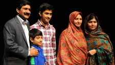 Malala Yousafzai stands with her family in England