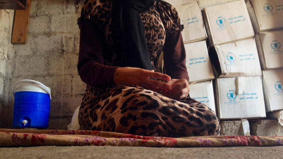 A 15-year-old Yazidi girl captured by the Islamic State group and forcibly married to a militant in Syria sits on the floor of a one-room house she now shares with her family after escaping in early August, while speaking in an interview with The Associated Press in Maqluba, Iraq, Wednesday, Oct. 8, 2014. (AP / Dalton Bennett)