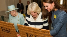 Queen Elizabeth II, left, the Duchess of Cornwall and the Duchess of Cambridge, right, looking at their hampers after being presented with gifts in Fortnum and Mason store in central London, Thursday, March 1, 2012. (AP Photo/Leon Neal, pool)