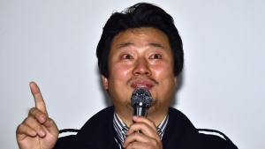 """South Korean director Lee Sang-Ho speaks at a guest visit event after a screening of his film """"Diving Bell, The Truth Shall Not Sink with Sewol,"""" during the 19th Busan International Film Festival. (AFP PHOTO / JUNG YEON-JE)"""
