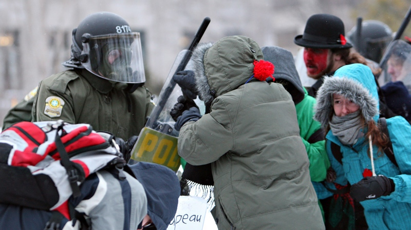 Demonstrators push on riot police officers as students protest tuition hikes Thursday, March 1, 2012 in front of the legislature in Quebec City. (Jacques Boissinot / THE CANADIAN PRESS)