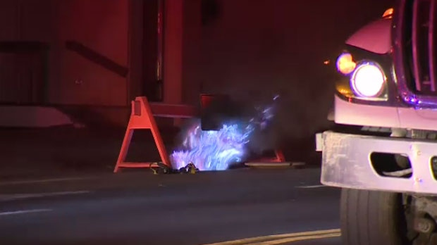 Underground electrical fire in downtown Calgary - flames leaping up through manhole.