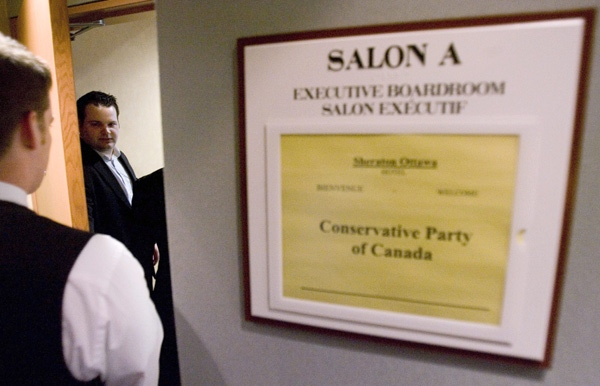 Conservative Party employee Ryan Sparrow opens the door to a secret briefing to select media on an RCMP search warrant, at a hotel in Ottawa, Sunday, April 20, 2008. (Tom Hanson / THE CANADIAN PRESS)