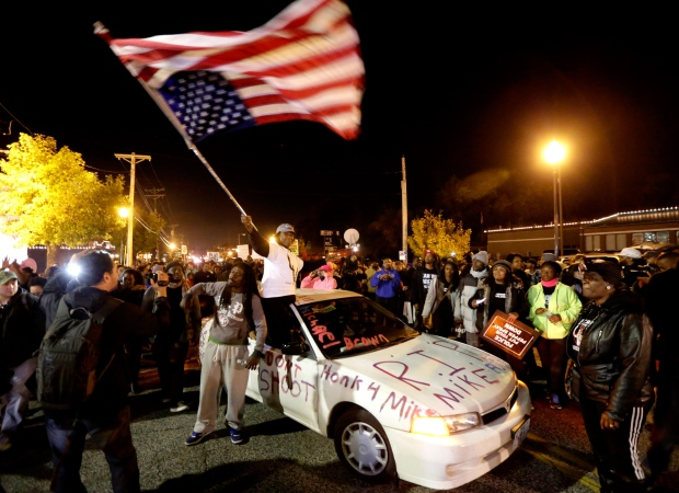 Protesters arrive at the Ferguson Police Department Saturday, Oct. 11, 2014, for a rally in remembrance of Michael Brown in Ferguson, Mo. (AP / Charles Rex Arbogast)