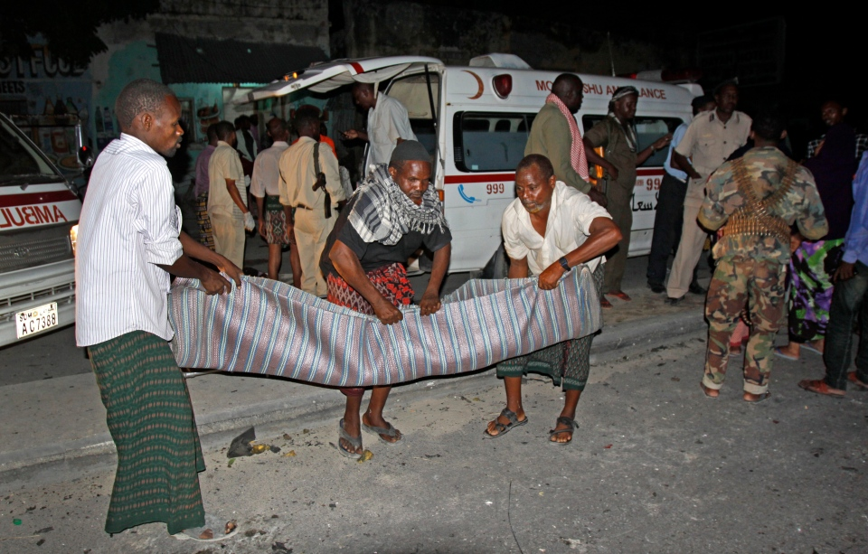 Somalis carry away a body from the scene of a car bomb attack in the capital Mogadishu, Somalia Sunday, Oct. 12, 2014. (AP / Farah Abdi Warsameh)