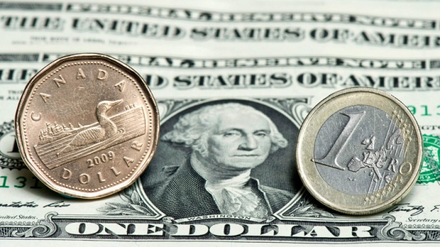 A Canadian dollar, left, and a Euro are seen next to a series of U.S. dollars. (Paul Chiasson / THE CANADIAN PRESS)