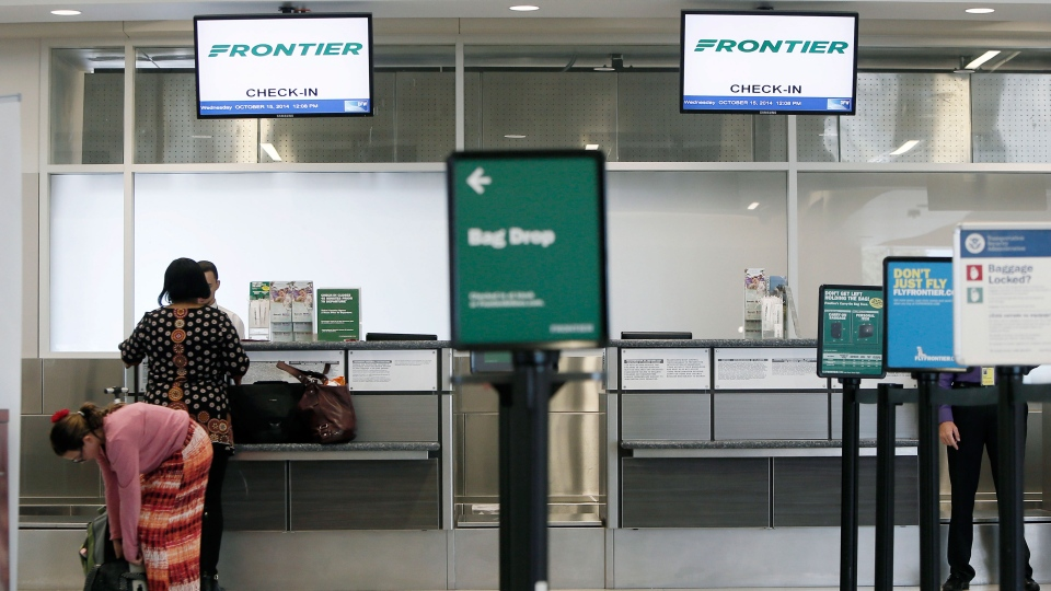 A Frontier Airlines employee wears gloves as she directs passengers where to go at Cleveland Hopkins International Airport, in Cleveland, Wednesday, Oct. 15, 2014. (AP / Tony Dejak)