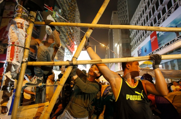 Supporters of the pro-democracy student protest construct bamboo barricades at an occupied intersection in the Mong Kok district of Hong Kong, Wednesday, Oct. 15, 2014. (AP / Wally Santana)