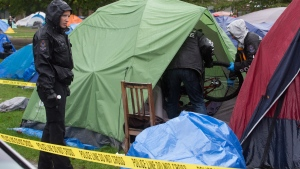 Police officers remove a brand new bike from a tent where a man was found dead at a tent city at Oppenheimer Park in the Downtown Eastside of Vancouver, on Wednesday, Oct. 15, 2014. (Darryl Dyck / THE CANADIAN PRESS)