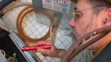 Dara Bowser, a building technologist who designs HVAC systems, inspects the heating system in Bev Craddock's home in this undated photo.
