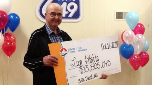 Retired fisherman Leon Hirtle collects a cheque for $13.8 million at the Bridgewater Curling Club Thursday morning.