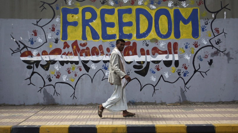 """A Yemeni walks past a graffiti that reads """"Freedom is made by people"""" on a street where protestors demanded the trial for the former President Ali Abdullah Saleh, in Sanaa, Yemen, Friday, March 2, 2012."""