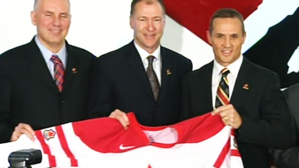 Steve Yzerman, right, holds up a jersey after it is announced that he is going to lead Team Canada into the 2014 Sochi Olympics on Monday, March 5, 2012.