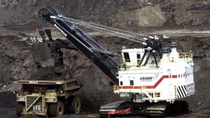 A hydraulic shovel loads a heavy hauler at an oilsands mine north of Fort McMurray, Alta. on June 19, 2003. (Adrian Wyld / THE CANADIAN PRESS)