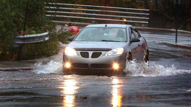 A car moves through a puddle in St.John's, N.L., Sunday, Oct.19, 2014. It was wet and windy, but southeastern Newfoundland received only a glancing blow from hurricane Gonzalo as the storm tracked offshore of the island overnight Sunday. (Paul Daly  / THE CANADIAN PRESS)