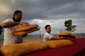 Bakers put the final touches on a giant 'koulouri' (bread ring similar to a bagel or pretzel) that encircled the medieval White Tower, in the northern Greek port city of Thessaloniki October 19, 2014. The 165-m diameter product weighed 1.35 tons before baking to compete for Guinness World Record.  (AP / Grigoris Siamidis)