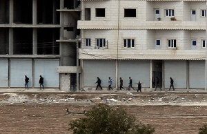 Kurdish fighters walk to their positions in Kobani, Syria, Sunday, Oct. 19, 2014. (AP Photo/Levend Ali)