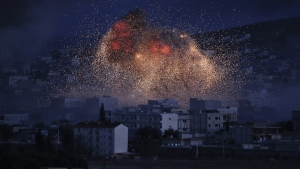 Thick smoke and flames from an airstrike by the U.S.-led coalition rise in Kobani, Syria, as seen from a hilltop on the outskirts of Suruc, at the Turkey-Syria border, Monday, Oct. 20, 2014. (AP Photo)
