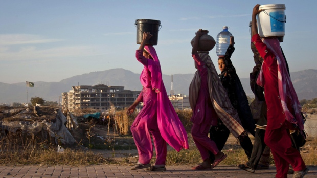 Pakistani girls walk home after collecting drinking water from a nearby point on the outskirts of Islamabad, Pakistan Wednesday, Dec. 14, 2011. (AP Photo/Anjum Naveed)