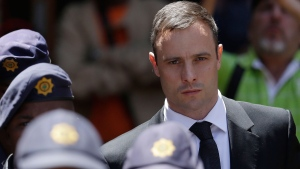 Oscar Pistorius escorted by police officers leaves the high court in Pretoria, South Africa, Friday, Oct. 17, 2014. (Themba Hadebe/AP)