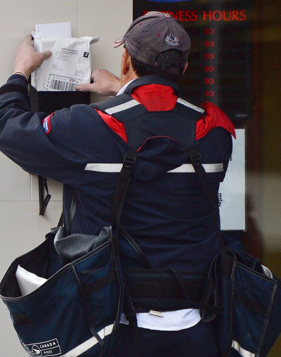 A mail carrier delivers mail in Ottawa, on Dec. 11, 2013. (Sean Kilpatrick / THE CANADIAN PRESS)