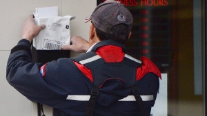 A mail carrier delivers mail in Ottawa, on Dec.11, 2013. (Sean Kilpatrick / THE CANADIAN PRESS)