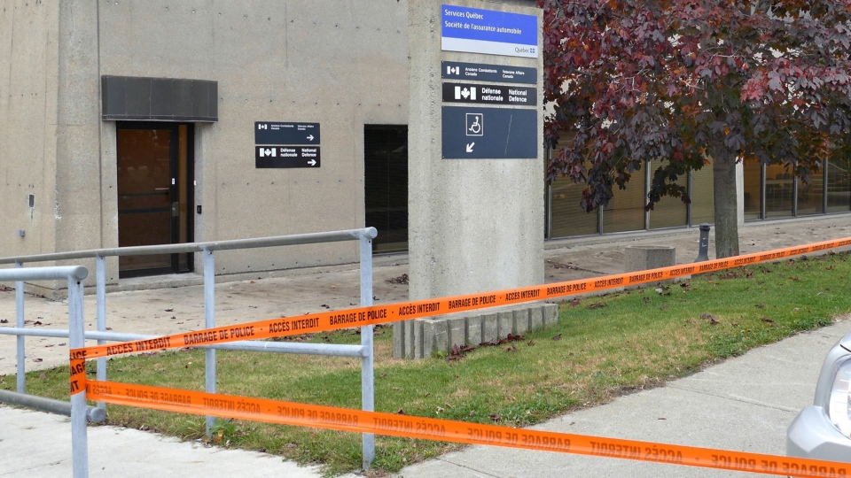 A sign for National Defence and Veterans Affairs is pictured next to a cordoned off area in St-Jean-sur-Richelieu on Monday, Oct. 20, 2014. (Pascal Marchand / THE CANADIAN PRESS)