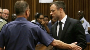 Oscar Pistorius, right, is led out of court in Pretoria, South Africa, Tuesday, Oct. 21, 2014. (AP / Themba Hadebe)