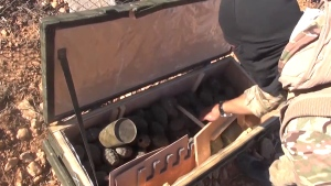 This screen grab from video posted on Monday, Oct. 21, 2014 and corresponding to reporting by the Associated Press shows an Islamic State fighter opening a box of German-made grenades in Kobani, Syria. (A3maq News / YouTube)