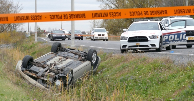 WARNING: Graphic content - Quebec police are investigating a hit-and-run in St-Jean-sur-Richelieu, Que. that left one soldier dead and another injured.<br><br>A car is overturned in the ditch in a cordoned off area in St-Jean-sur-Richelieu, Que. on Monday, Oct. 20, 2014. (Pascal Marchand / THE CANADIAN PRESS)