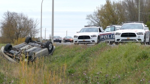 Police cruisers are parked next to an overturned car in St-Jean-sur-Richelieu, Que. on Monday Oct. 20, 2014. (Pascal Marchand / THE CANADIAN PRESS)