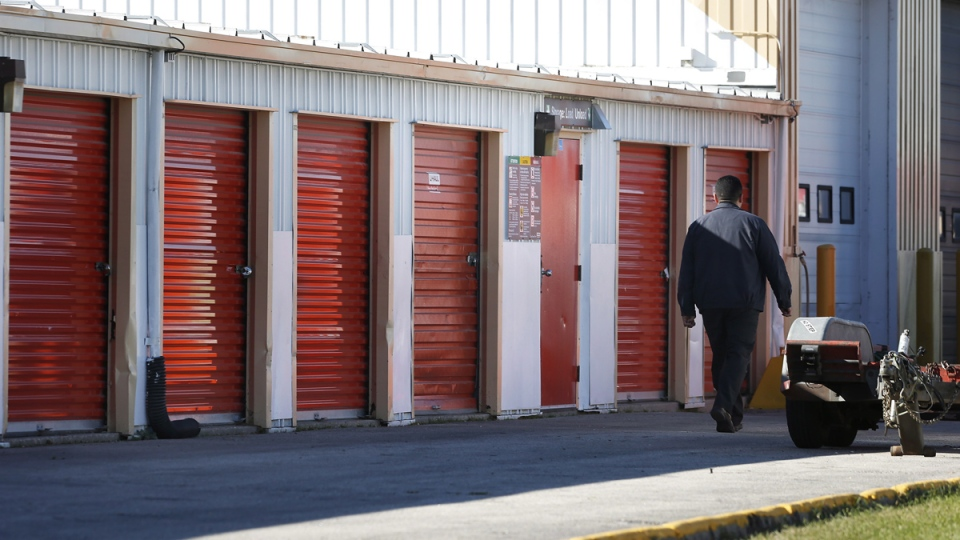 Company security staff walk past storage lockers in Winnipeg, on Oct. 21, 2014. (John Woods / THE CANADIAN PRESS)