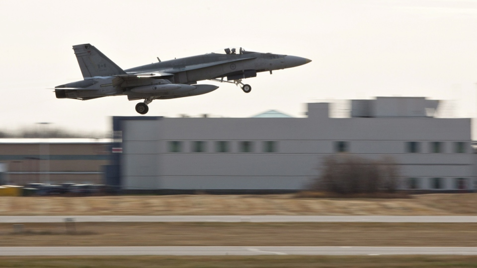 A pilot takes off during the departure of CF-18 Hornets in support of Operation IMPACT, in Cold Lake, Alberta on Tuesday, Oct. 21, 2014. (Jason Franson / THE CANADIAN PRESS)