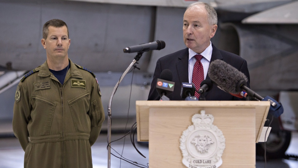 Minister of National Defence Rob Nicholson, right, and Colonel Eric Kenny speak about Operation IMPACT, after the departure of CF-18 Hornets in Cold Lake, Alta. on Tuesday Oct. 21, 2014. (Jason Franson / THE CANADIAN PRESS)