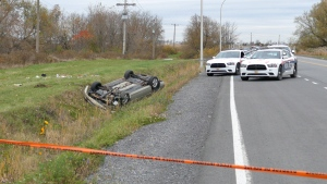 A car is overturned in the ditch in a cordoned off area in Saint-Jean-sur-Richelieu, Que. on Monday, Oct. 20, 2014. (Pascal Marchand / THE CANADIAN PRESS)