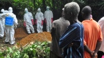 People attend the funeral of a woman suspected to have died from Ebola virus in Monrovia, Liberia. Saturday, Oct, 18, 2014. (AP / Abbas Dulleh)