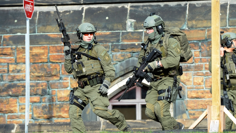 An RCMP intervention team run next to a Parliament building in Ottawa, Wednesday Oct. 22, 2014.  (Adrian Wyld / THE CANADIAN PRESS)