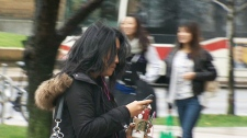 A woman is seen with a smartphone.