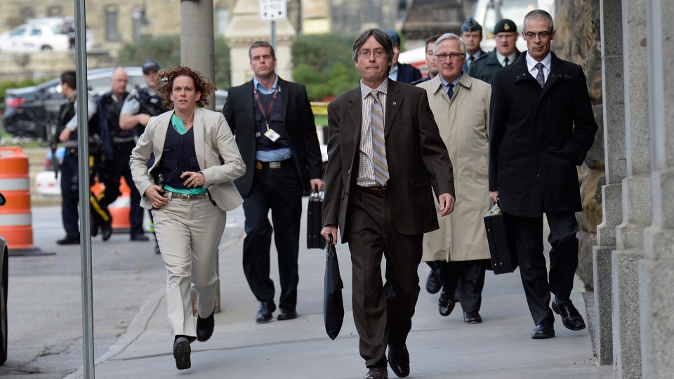 Parliamentary staff, including CSIS head Richard Fadden (second from right) leave the area after a shooting on Parliament Hill in Ottawa on Wednesday Oct. 22, 2014.  (Adrian Wyld / THE CANADIAN PRESS)