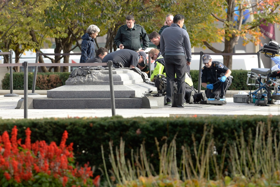 A soldier, police and paramedics tend to a soldier shot at the National Memorial near Parliament Hill in Ottawa on Wednesday, Oct. 22, 2014. The soldier has since died. (Adrian Wyld / THE CANADIAN PRESS)