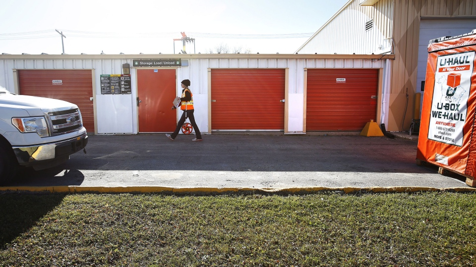 Companay staff walk past storage lockers in Winnipeg, Tuesday, October 21, 2014. Police in Winnipeg say they have discovered the remains of dead infants in a city storage locker. (John Woods  / THE CANADIAN PRESS)