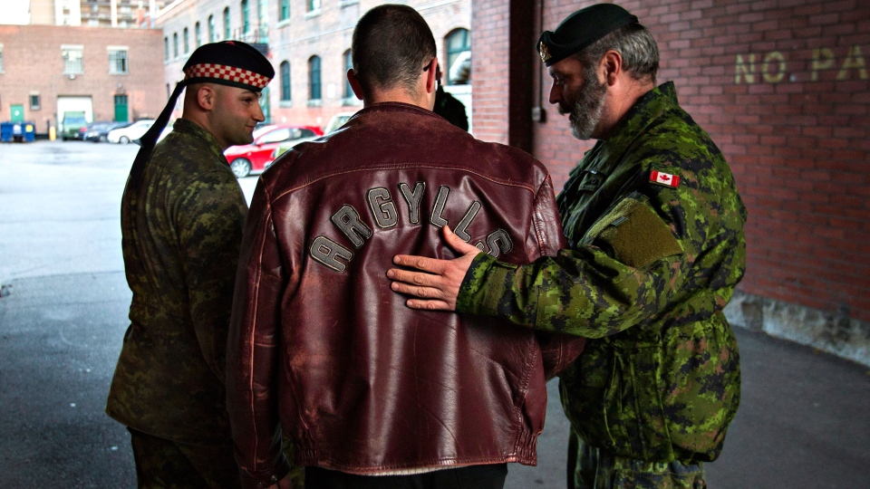 A man in an Argylls jacket is comforted by fellow soldiers after placing flowers in memory of soldier Nathan Cirillo outside the gates of the John Weir Foote Armoury, the home of the Argyll and Sutherland Highlanders of Canada in Hamilton, Ont., Wednesday, Oct. 22, 2014. (Aaron Lynett / THE CANADIAN PRESS)